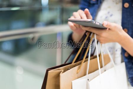 mujer de compras usando el telefono