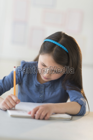 schoolgirl 8 9 writing in notebook