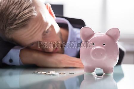 hombre deprimido mirando monedas y piggybank
