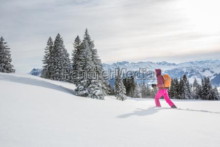 bonita joven mujer raquetas de nieve