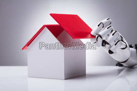 robot building house with red roof