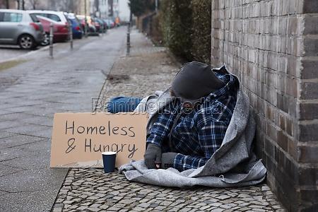 mendigo masculino acostado en la calle