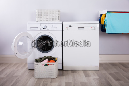 lavadora vacia con montones de ropa