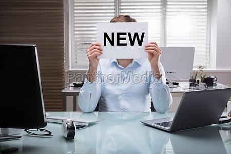 empresario sosteniendo carteles con texto nuevo