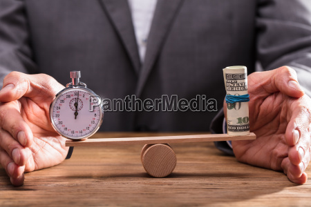 businessperson balancing stopwatch and rolled up