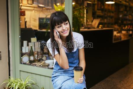 mujer sonriente sentada en la puerta