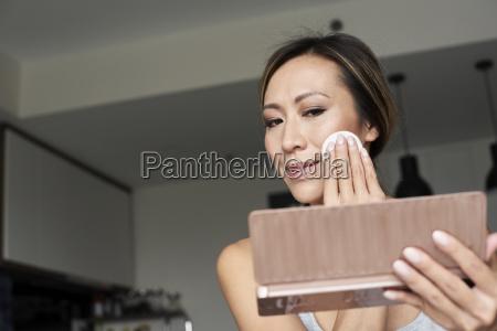 mujer en casa usando espejo de