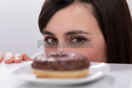young woman looking at donut