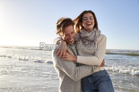 pareja divirtiendose en la playa de