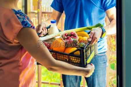 mujer aceptando comestibles caja de entrega
