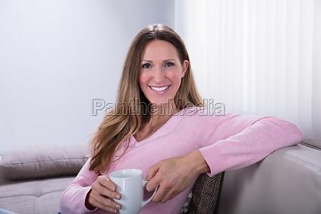 mujer feliz sentada en el sofa