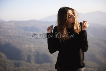woman playing with hair while standing