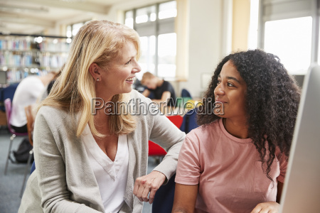 teacher and female student work on