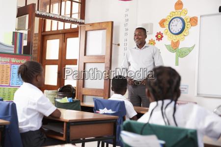 teacher welcomes kids sitting in elementary