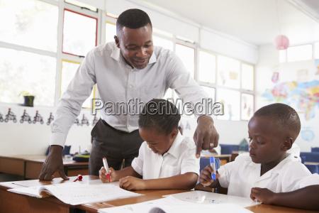teacher stands helping elementary school kids
