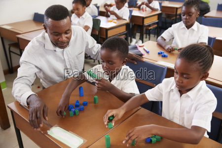teacher helping elementary school kids counting