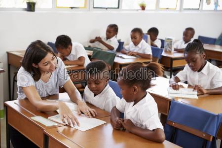 volunteer teacher helping school kids at