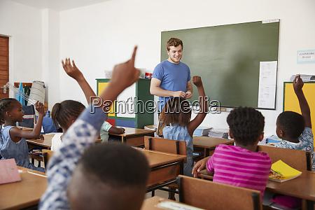 kids raising hands to teacher in