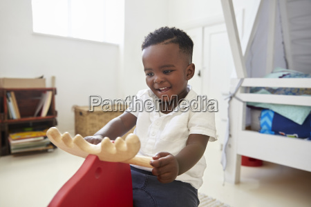 young boy sitting on ride on