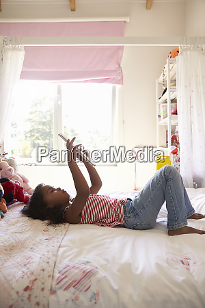 young girl lying on bed using