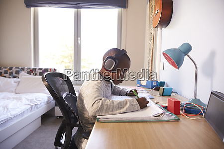 young boy in bedroom wearing headphones