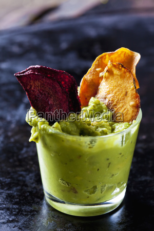 glass of guacamole and vegetable chips