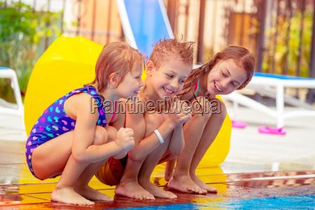 ninyos felices cerca de la piscina