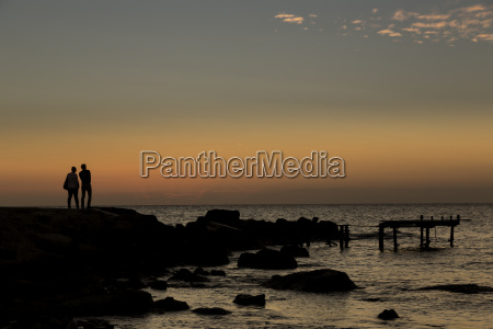 silhouette of two people standing at