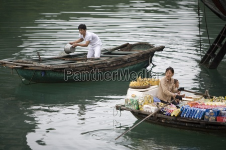 woman with supplies in boat beside