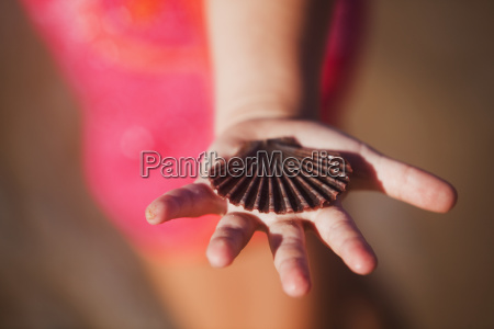 a hand holding a seashell gold