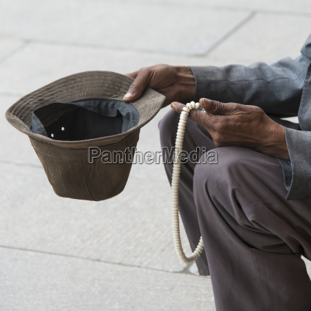 man holding out hat for money