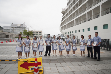 cruise ship employees holding letter signs