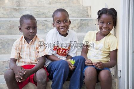 three children sitting on a step