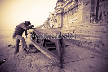 man constructing boat varanasi india