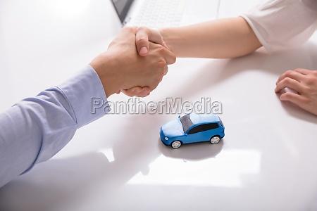 concesionario de coches estrechando la mano