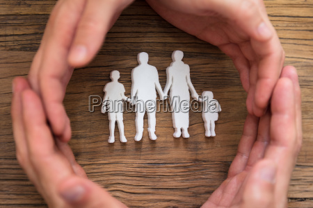 mano de pareja protegiendo figuras familiares