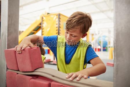 schoolboy building with toy bricks at