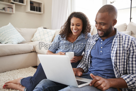 young black couple using laptop sitting