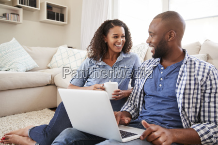 young black couple using laptop at