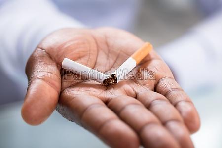 hand holding broken cigarette