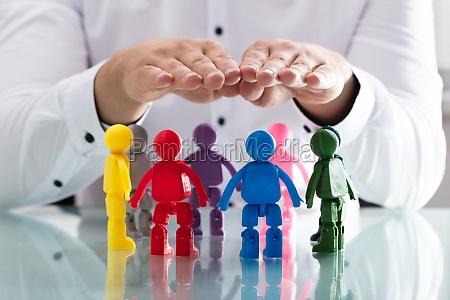 persona que protege figuras humanas multicolores