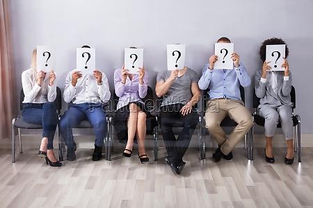 personas sosteniendo signo de interrogacion