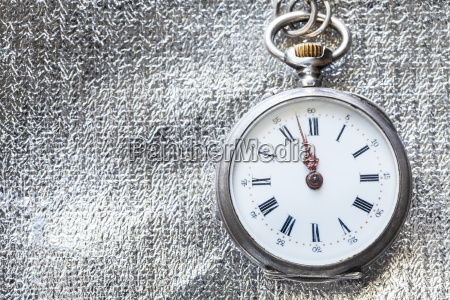 retro pocket watch on silver fabric