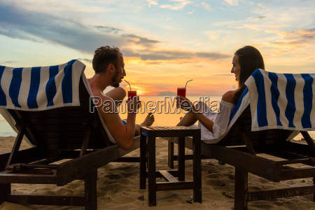 young couple drinking cocktails on a