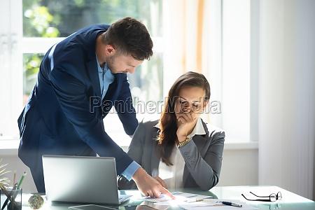 empresario explicando grafico a triste empleada