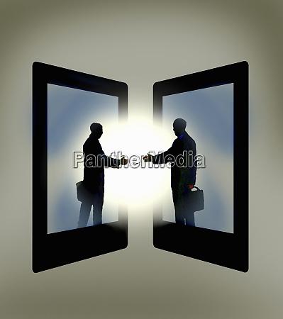 two businessmen emerging from digital tablets