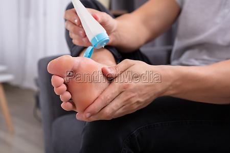 hombre aplicando crema en sus pies