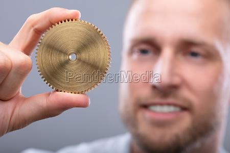 man holding golden gear