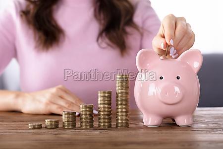 mujer insertando moneda en piggybank