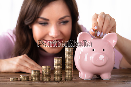 happy young woman inserting coin in